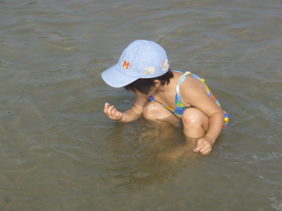 蛇の目ビーチで、小さな貝を見つける子ども